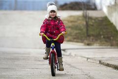 Beautiful smiling little girl riding bicycle in a park.  Royalty Free Stock Photos