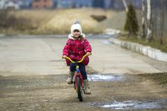 Beautiful smiling little girl riding bicycle in a park Stock Photo