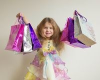 Beautiful smiling little girl with shopping bags. Fashion girls shopping. Beautiful smiling little girl with shopping bags and gifts. Happy child holds a lot of Stock Photo