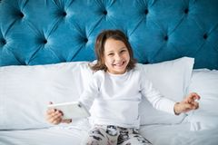 Beautiful smiling little girl taking selfie on smartphone while lying in bed. Beautiful smiling little girl taking selfie on smartphone while lying in soft bed Stock Photo