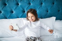 Beautiful smiling little girl taking selfie on smartphone while lying in bed. Beautiful smiling little girl taking selfie on smartphone while lying in soft bed Royalty Free Stock Photos