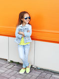 Beautiful smiling little girl wearing a sunglasses and jeans clothes. In city Royalty Free Stock Photography