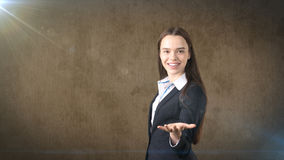 Beautiful smiling longhair brunette businesswoman showing something invisible in front of her with copyspace Stock Images