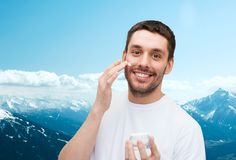 Beautiful smiling man applyin cream Royalty Free Stock Images