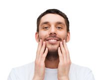 Beautiful smiling man touching his face Stock Photo