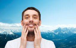 Beautiful smiling man touching his face Stock Images
