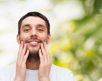 Beautiful smiling man touching his face. Health and beauty concept - beautiful smiling man touching his face Royalty Free Stock Photos