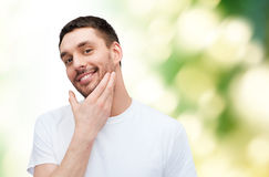 Beautiful smiling man touching his face Royalty Free Stock Image