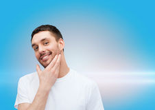 Beautiful smiling man touching his face Stock Photos