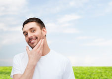 Beautiful smiling man touching his face Stock Image