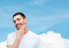 Beautiful smiling man touching his face Royalty Free Stock Images