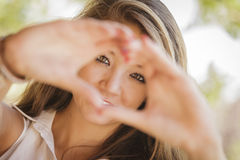 Beautiful Smiling Mixed Race Teen Portrait doing Heart Hand Sign Royalty Free Stock Image