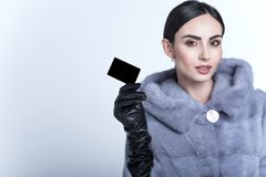 Beautiful smiling model wearing blue mink fur coat and long leather gloves holding black blank business card. Beautiful smiling dark-haired model with sleek low Stock Photo