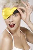 Beautiful smiling model wearing a yellow sleep mask Stock Image