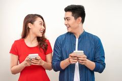 Beautiful smiling modern couple in casual wear with phones in hands on a white wall background.  royalty free stock photo