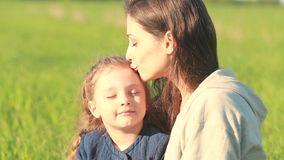 Beautiful smiling mother embracing her cute daughter with yellow stock video footage