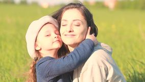 Beautiful smiling mother embracing her cute daughter stock footage