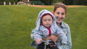 Beautiful smiling mother holding baby son and walking at park stock video footage