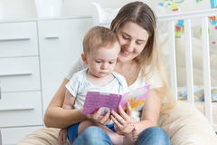 Beautiful smiling mother reading book to her 9 months old baby b Stock Images