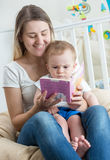 Beautiful smiling mother reading story to her 9 months old baby Stock Photo