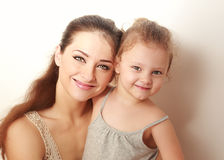 Beautiful smiling mother and small happy daughter cuddling Stock Images