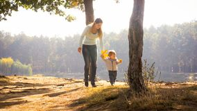 Beautiful smiling mother with toddler son walking in park at sunny day. Smiling mother with toddler son walking in park at sunny day Royalty Free Stock Photos