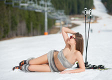 Beautiful smiling naked skier is lying on snowy slope near ski lift at ski resort Stock Images