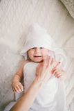 Beautiful smiling newborn baby boy covered with white bamboo towel with fun ears. lies on a white knit, wool plaid bright interior Royalty Free Stock Photography