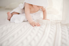 Beautiful smiling newborn baby boy covered with white bamboo towel with fun ears. Sitting on a white knit, wool plaid bright inter Stock Photography