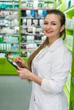 Beautiful and smiling pharmacist working with tablet royalty free stock images