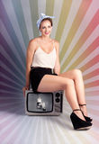 Pinup Housewife Sitting On Vintage Television Set. Beautiful Smiling Pin-up Girl Sitting On A Black And White Vintage TV Set In A Depiction Of Retro Technology Royalty Free Stock Image