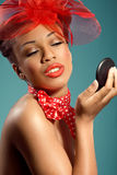 Beautiful smiling pinup girl checking makeup Stock Images