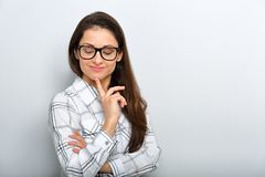 Beautiful smiling positive successful business woman in glasses looking down with finger under the face stock images