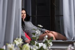 Beautiful smiling pregnant brunette woman in a knitted dress sit Stock Photos