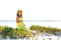 Beautiful smiling pregnant woman with flowers sitting on a beach Stock Image