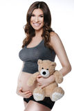 Beautiful smiling pregnant woman with plush toy Stock Image