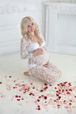 Beautiful smiling pregnant woman sitting on floor with red rose Stock Photo