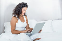 Beautiful smiling pregnant woman using laptop Royalty Free Stock Images