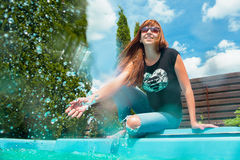 Beautiful smiling red hair girl near swimming pool. In summer Stock Photo