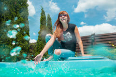 Beautiful smiling red hair girl near swimming pool. In summer Royalty Free Stock Images