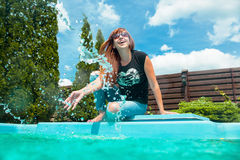 Beautiful smiling red hair girl near swimming pool. In summer Royalty Free Stock Image