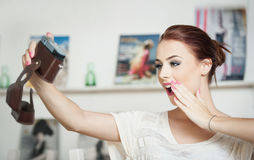 Beautiful, smiling red hair woman taking photos of herself with a camera. Fashionable attractive female taking a self portrait Royalty Free Stock Photo