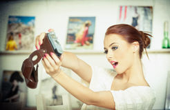 Beautiful, smiling red hair woman taking photos of herself with a camera. Fashionable attractive female taking a self portrait Stock Images