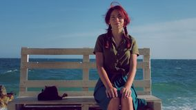 Beautiful smiling red-haired traveler girl sitting on a bench on the sea beach, dreams, relaxes and enjoys life. In the background, sea waves and blue cloudy stock video