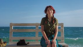 Beautiful smiling red-haired traveler girl sitting on a bench on the sea beach, dreams, relaxes and enjoys life. In the background, sea waves and blue cloudy stock footage