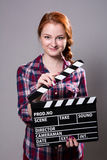 Beautiful smiling red-haired woman holding a movie clapper Royalty Free Stock Photo