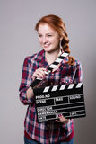 Beautiful smiling red-haired woman holding a movie clapper Royalty Free Stock Photos