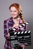 Beautiful smiling red-haired woman holding a movie clapper. Stock Image