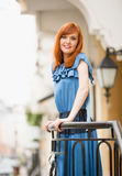 Beautiful smiling redhead girl in blue dress posing on street Stock Photo