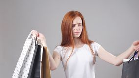 Beautiful smiling redhead girl with a lot of shopping bags. stock video